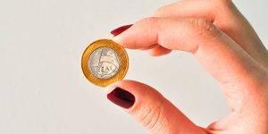 Mano sosteniendo una moneda