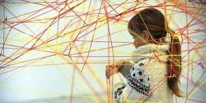Una niña participa en una actividad con redes de lana en el Museo CAJAGRANADA