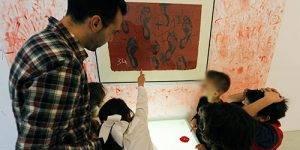 Niños de espaldas aprenden sobre arte con un docente