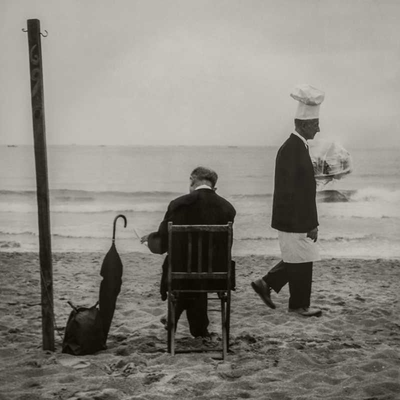 Fotografía de un caballero sentado y un camarero caminando junto al mar
