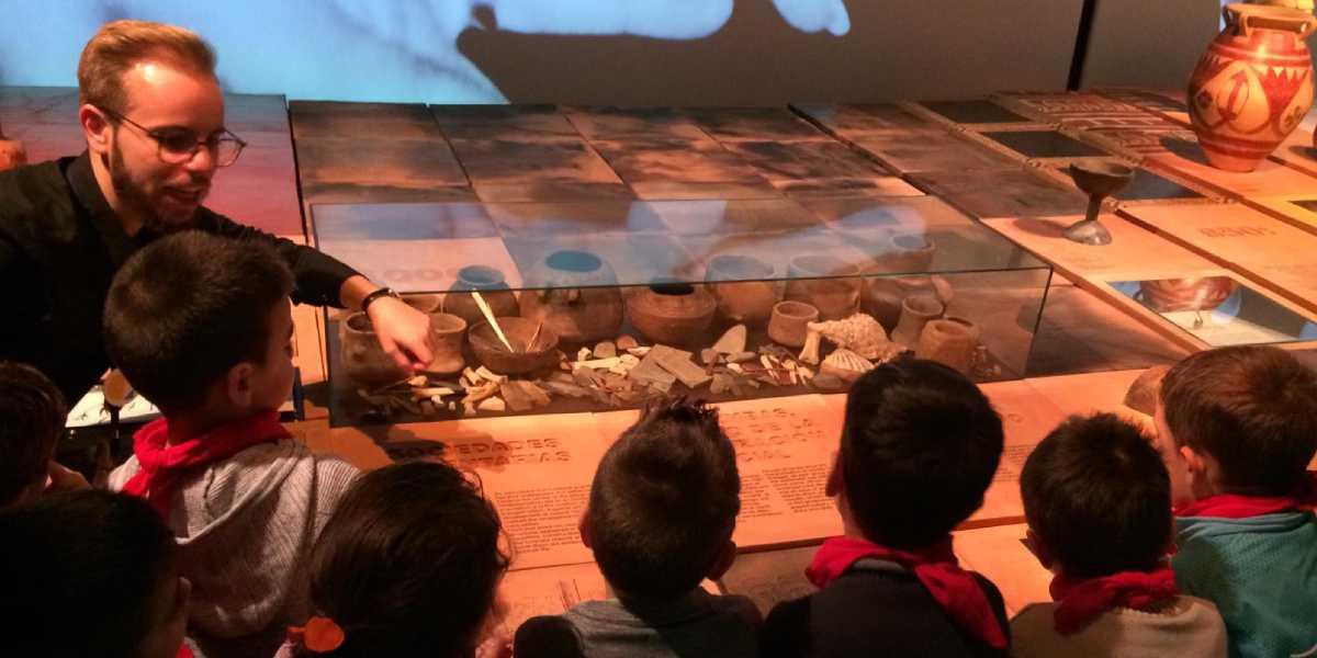 Varios niños atienden a una explicación sobre utensilios prehistóricos de un mediador cultural del Museo Memoria de Andalucía